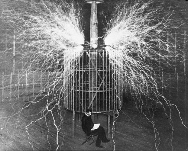 Nikola Tesla, seen here reading by the light of  his Wardenclyff Tower.