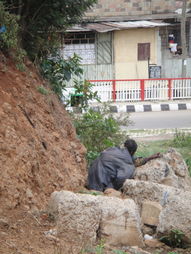 Man shitting in the street in Addis Ababa