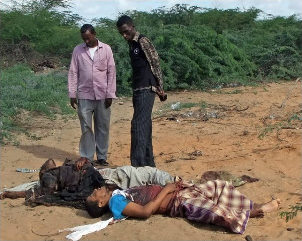 Men looked at the body of Fazul Abdullah Mohammed, front right, and another unidentified man in Mogadishu, Somalia, on Wednesday.