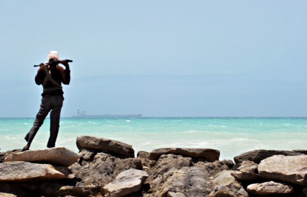 A pirate stands on a rocky outcrop on the coast in Hobyo, central Somalia, on Aug. 20, 2010. A hijacked Korean supertanker is anchored on the horizon.