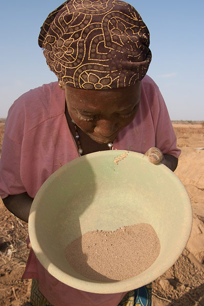 Women sweep up the dust from the process and pan it for any gold that might have been missed