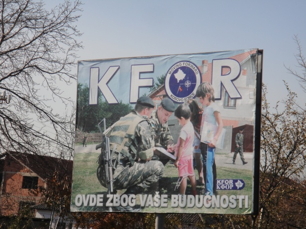 Signs promoting the positive impact of international troops in an effort to reduce tensions inside Kosovo
