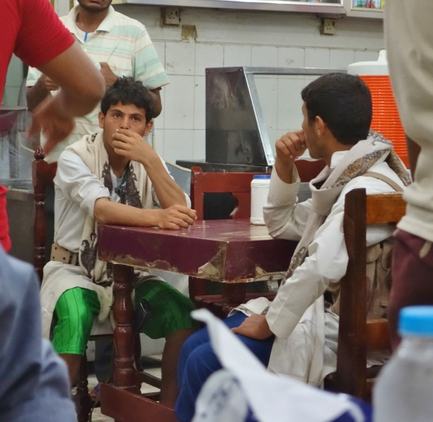 a-houthi-rebel-fighter-cradles-his-rifle-while-waiting-for-dinner-inside-of-a-crowded-fish-restaurant-in-hodeida-shortly-after-the-rebels-seized-control-of-the-city