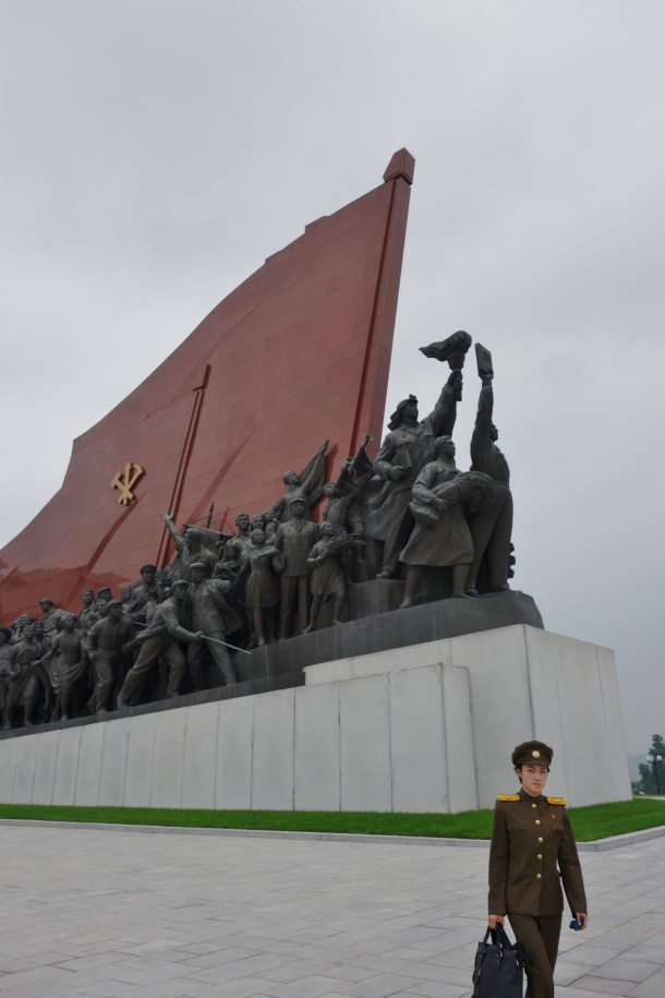 A female soldier walks past a militaristic statue in downtown Pyongyang