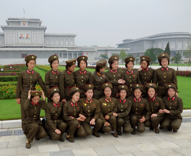 A group of soldiers prepare themselves for a group picture in front of the mausoleum housing Kim Il-sung and Kim Jong-Il